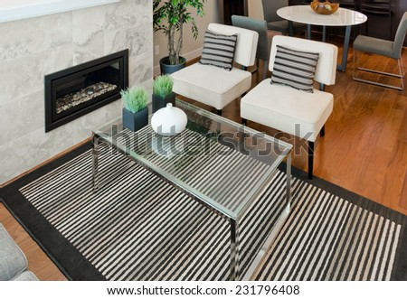 Outlook at the luxury modern living suite : two modern chairs with nicely decorated coffee table and dining room and kitchen at the back Interior design of a new house. - stock photo
