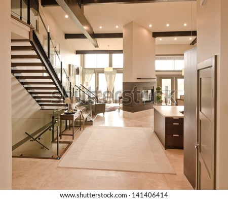 Outlook at the luxury spacious modern living room with the fireplace and stairs to the upper level. Interior design. - stock photo