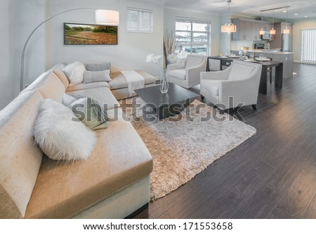 Outlook, panorama at the luxury modern living suite, room with sofa and chairs and dining table and the kitchen at the back. Interior design of a brand new townhouse. - stock photo