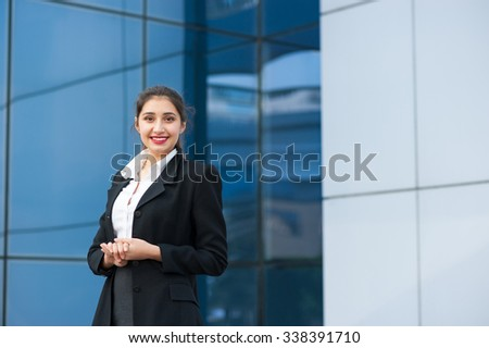 Outoor portrait of a beautiful smiling young business woman with modern building as background. - stock photo