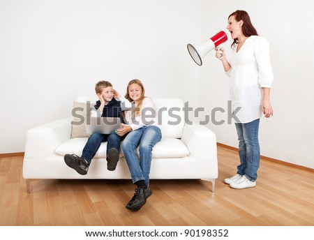 Outrageous mom screaming at kids with laptop using megaphone - stock photo