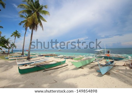 Outrigger canoes on a tropical beach with palm trees - stock photo
