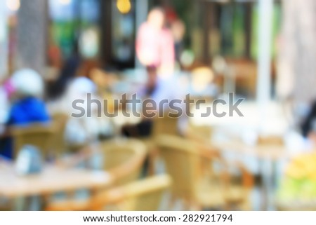 Outside cafe on the open air, blurred background with bleached unrecognizable people - stock photo