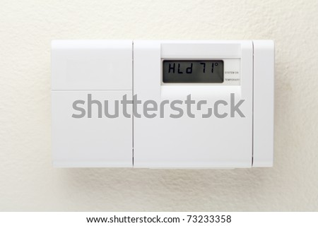Outside of a white heating, ventilating, and air conditioning control panel on a wall. - stock photo
