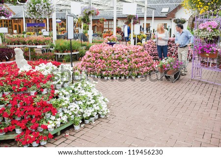 Outside of garden center with many types of plants and flowers and couple pushing a trolley - stock photo