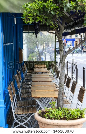 Outside part of the french restaurant in Paris with it's wooden tables in a row facing a street and a potted plant for decoration.