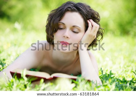 outside portrait of beautiful curly girl laying on grass and reading book in park - stock photo