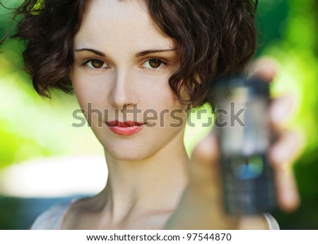 outside portrait of beautiful young curly woman with mobile phone in park - stock photo