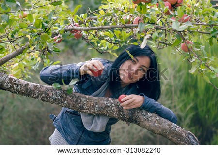 outside portrait of beautiful young girl with red apple in forest - stock photo