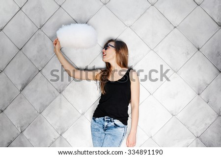 Outside portrait of naughty young blonde girl having fun on the date. Posing with cotton candy near gray wall