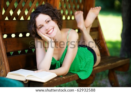 outside portrait of young beautiful happy woman laying on bench and reading book in park - stock photo