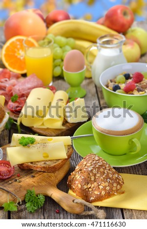 Outside served colorful breakfast with a large selection of food and a cup of cappuccino, blue sky in the background