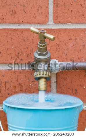 Outside tap on brick wall filling a blue bucket - stock photo