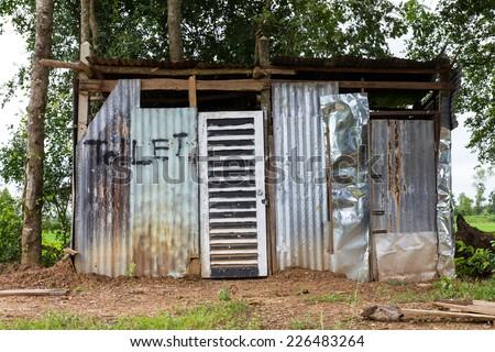 Outside toilet made of zinc nestled among the trees. - stock photo