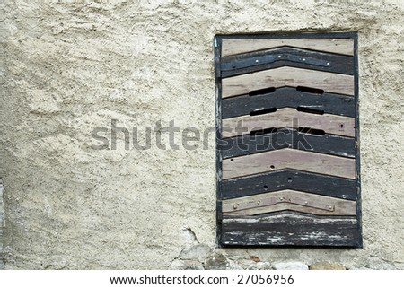 outside view on old locked jail window with a wood shutter