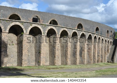 Outside walls of an ancient roman amphitheater, showing massive buttresses and raised arches in perfect condition