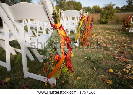 Outside wedding scene with white chairs and leaves in the grass - stock photo