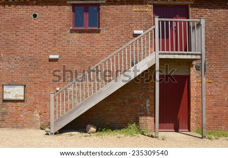 Outside wooden staircase on old brick wall to quayside building at Dell Quay in the Chichester Harbour. West Sussex. England - stock photo
