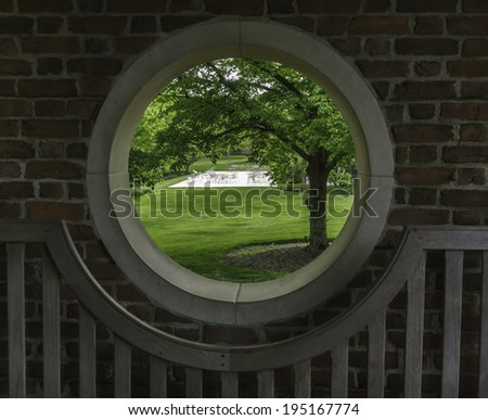 Outside world at a glance: Four-part porthole in a walled garden with a view of spacious green lawn, trees, and patio across the way - stock photo