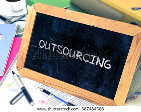 Outsourcing Handwritten by Chalk on a Blackboard. Composition with Small Chalkboard on Background of Working Table with Office Folders, Stationery, Reports. Blurred Background. Toned Image. 3D Render. - stock photo