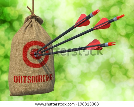 Outsourcing - Three Arrows Hit in Red Target on a Hanging Sack on Green Bokeh Background. - stock photo