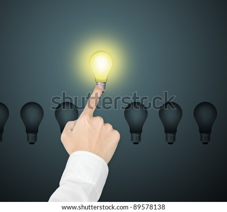 outstanding bright light bulb symbol of leading idea being pointed by male hand - stock photo