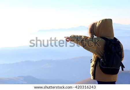 outstretched arm and pointing finger of young person with backpack in the mountains