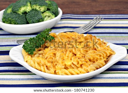 Oval bowl of spiral baked macaroni and cheese with a side dish of broccoli.  High angle view. - stock photo