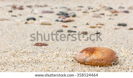 Oval shape orange rock on sand close up. Shallow depth of field. Selective focus on foreground rock. Blurred background of many stones of different shapes sizes and colors.  - stock photo