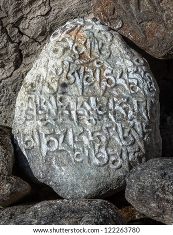 Oval stone along Everest trek on which carved ancient buddhist texts - Nepal, Himalayas - stock photo