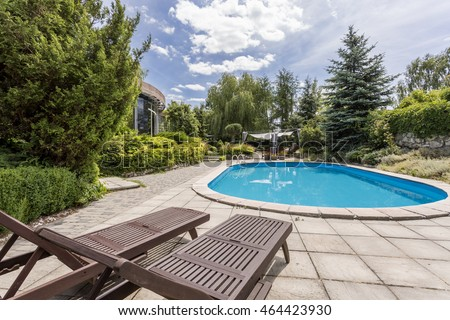Oval swimming pool and two deckchairs in a large garden of a modern house