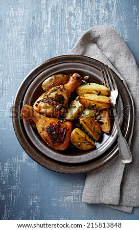Oven-baked chicken and potatoes with pumpkin seeds (autumn style) - stock photo