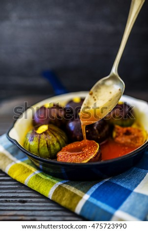 Oven-baked figs with spices, porto and honey on enamelled frying pan with spoon.