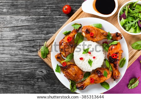 Oven baked golden sticky chicken drumsticks marinated with honey, soy sauce and ginger on a white dish with rice, pieces of chili pepper, spinach, chard and parsley, Asian flavors and style, top view - stock photo