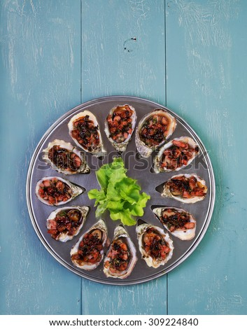 Oven baked oysters kilpatrick on special cooking and serving metal tray - stock photo