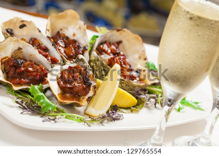 Oven baked oysters kilpatrick with glasses of champagne - stock photo
