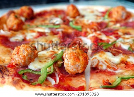 Oven baked pizza with meatballs, salami, tomatoes, cheese and fresh bell peppers. This image uses selective focus and shallow depth of field.