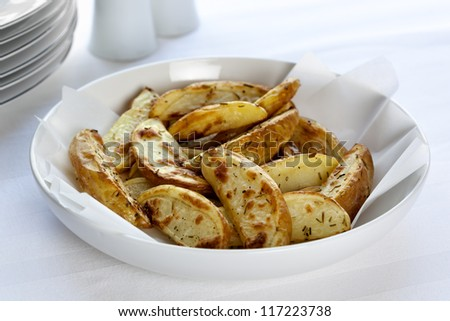 Oven-baked potato wedges in white serving bowl, sprinkled with rosemary.