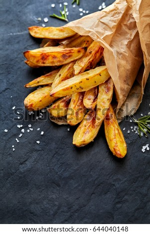 Baked potato fries addition sea salt stock photo 644040136 oven baked potato wedges with sea salt and rosemary on a black background ccuart Image collections