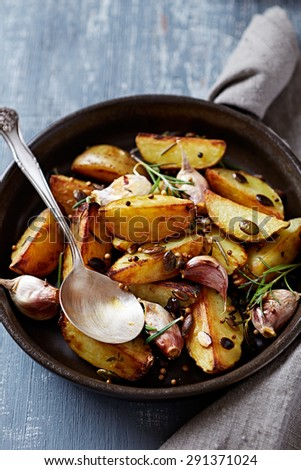 Oven-baked potatoes with pumpkin seeds, garlic and herbs   - stock photo