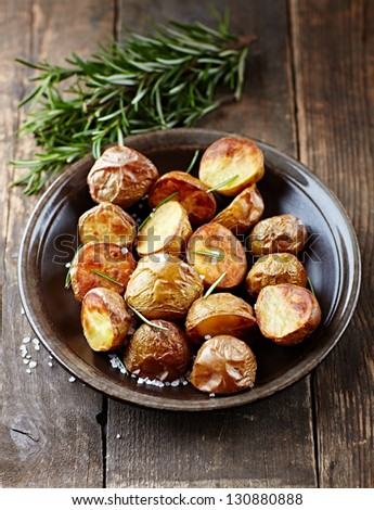 Oven-baked potatoes with sea salt and rosemary - stock photo