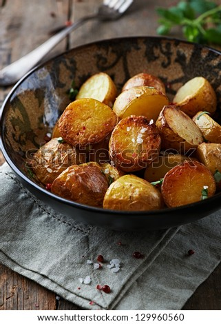 Oven baked potatoes with sea salt, pink pepper and herbs - stock photo