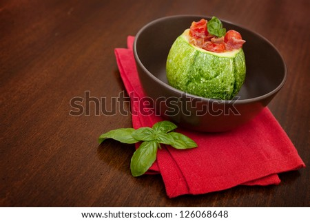 Oven baked round zucchini stuffed with egg, bacon and tomatoes - stock photo