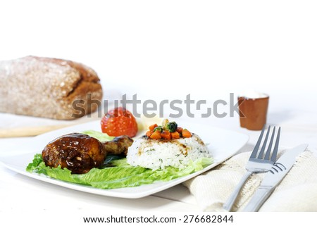 Oven cooked Chicken leg dish with rice side and vegetables and bread on bright white background