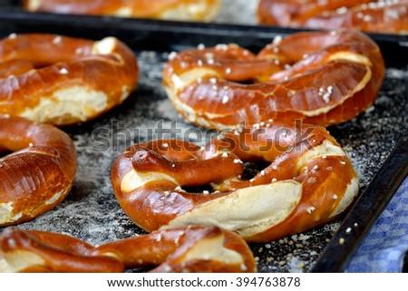 Oven fresh handmade crispy Bavarian pretzels on baking sheets - stock photo