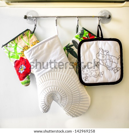 Oven gloves hanging in a row on the kitchen frige - stock photo