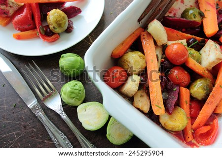Oven-pan with roasted vegetables with carrots, tomatoes, peppers, brussels sprouts and beetroots - stock photo