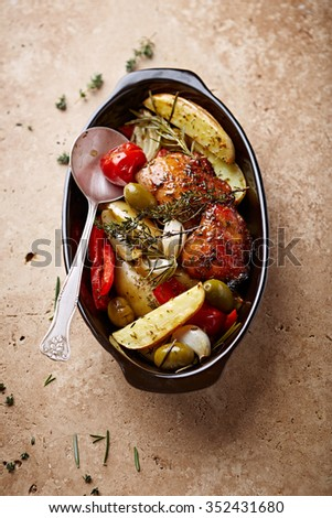Oven-roasted chicken and vegetables with herbs - stock photo