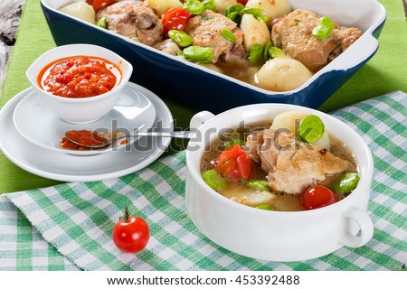 oven stew chicken things, new potatoes, tomatoes and butter lima beans in graten dish and in soup bowl on table mat, tomato and bell pepper sauce in gravy boat, view from above, close-up - stock photo