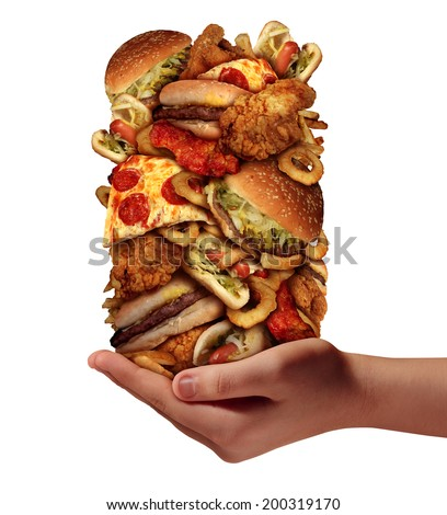 Over eating and compulsive indulgence of fast food concept as a hand holding up a huge stack of junk food as hamburgers hotdogs and french fries as an unhealthy diet and bad nutrition symbol. - stock photo